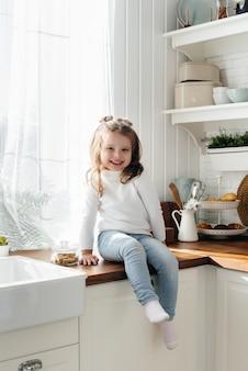 Kleines süßes mädchen, das in der küche, glück, familie spielt. kochen.