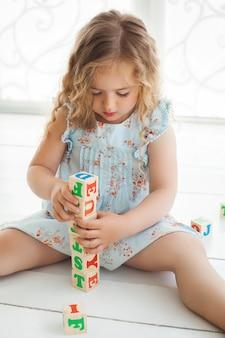 Kleines süßes mädchen, das mit abc-würfeln spielt und erzieht. hübsches mädchen, das alphabetblöcke baut. kind, das drinnen spielt.