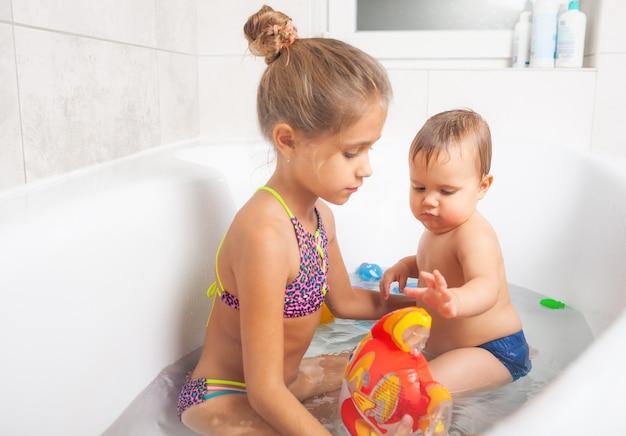 Kleines süßes mädchen, das mit ihrem kleinen bruder mit einem hellen aufblasbaren fisch spielt, während er in einer badewanne sitzt