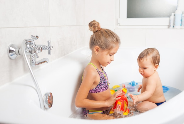 Kleines süßes mädchen, das mit ihrem kleinen bruder mit einem hellen aufblasbaren fisch spielt, während in einer badewanne mit wasser sitzt