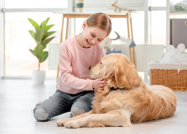Kleines süßes mädchen, das mit lächeln auf ihrem gesicht auf dem boden sitzt und golden retriever hund streichelt