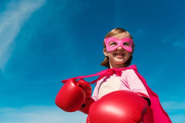 Kleines süßes mädchen, das superhelden spielt wir sind stolz darauf, hope zu unterstützen