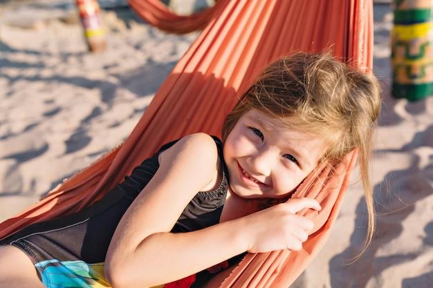 Kleines süßes mädchen gekleidet im schwarzen badeanzug am strand