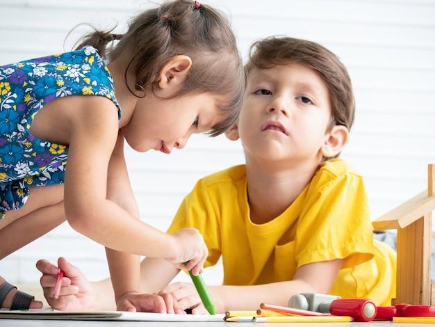 Kleines süßes mädchen glücklich, spielzeug zu spielen, während kleiner junge müde langweilig betonte, um zusammen zu spielen.