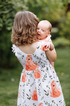 Kleines süßes mädchen hält eine neugeborene schwester in ihren armen und verbringt glückliche zeit mit ihr draußen