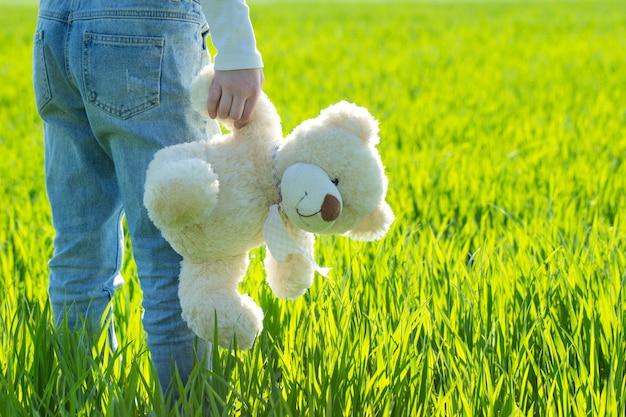 Kleines süßes mädchen im gras, das teddybär hält