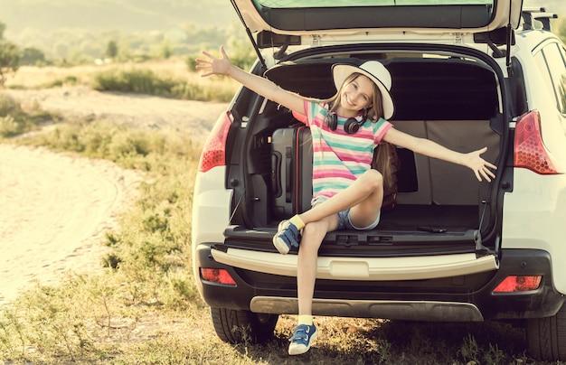 Kleines süßes mädchen im kofferraum eines autos mit koffern