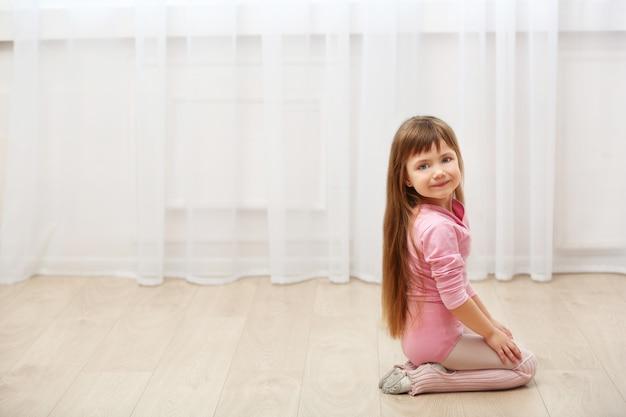 Kleines süßes mädchen im rosa trikot, das auf boden im tanzstudio sitzt