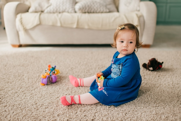 Kleines süßes mädchen im schönen kleid sitzt auf teppich und spielt mit ihren verschiedenen spielzeugen