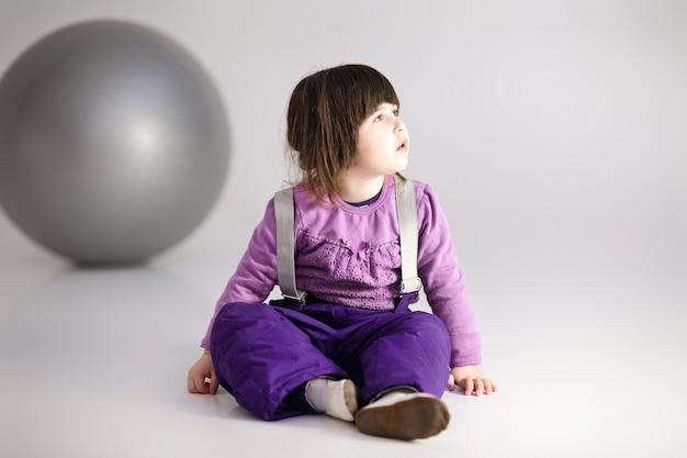 Kleines süßes mädchen in den lila kleidern mit einem großen ball für fitness auf grauem hintergrund.