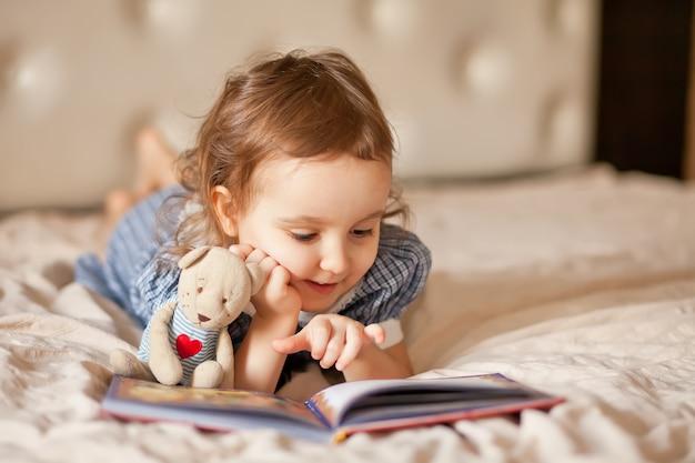 Kleines süßes mädchen in einem retro-kleid, das ein buch liest.