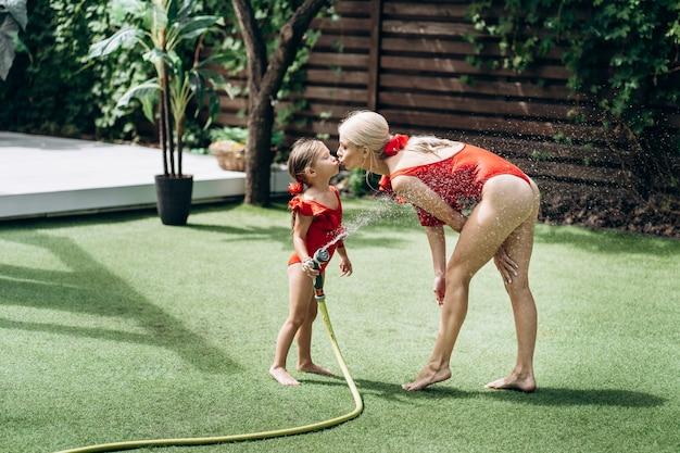 Kleines süßes mädchen in einem roten badeanzug küsst ihre mutter konzept der glücklichen kindheit