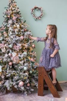 Kleines süßes mädchen in einem schönen kleid spielt mit dem weihnachtsbaum.