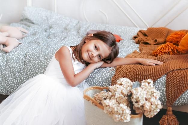 Kleines süßes mädchen in einem schönen weißen kleid entspannt sich in ihrem hellen schlafzimmer
