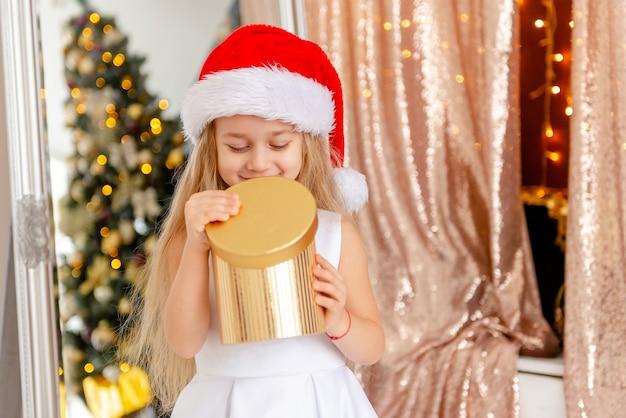 Kleines süßes mädchen in einem schönen weißen kleid in einer weihnachtsmütze öffnet ein weihnachtsgeschenk.