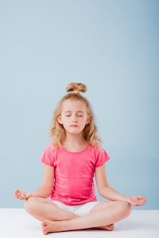 Kleines süßes mädchen in einer yoga-position