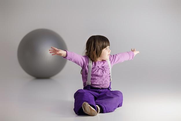 Kleines süßes mädchen in lila kleidern mit ausgestreckten armen und mit einem großen ball für fitness auf grauem hintergrund.