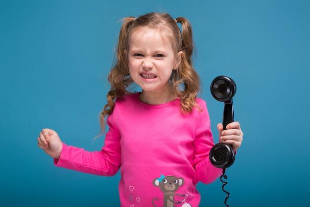 Kleines süßes mädchen in rosa hemd mit affen und blauer hose spricht ein telefon