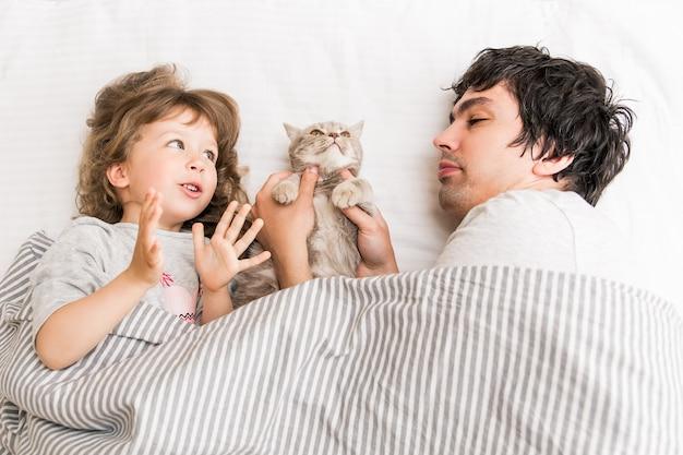 Kleines süßes mädchen liegt und spielt mit vater und katze auf der couch.