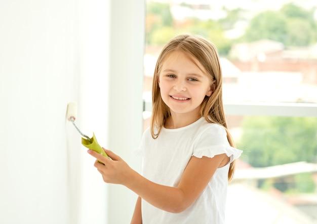 Kleines süßes mädchen malt eine wand mit farbroller