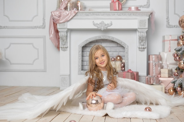 Kleines süßes mädchen mit blondem haar mit engelsflügeln im studio neben dem weihnachtsbaum