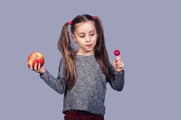 Kleines süßes mädchen mit einer süßigkeit und einem apfel in ihren händen. konzeptwahl zwischen gesundem und junk food. isoliert auf grauer oberfläche