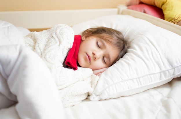 Kleines süßes mädchen mit kaltem schlafen unter decke