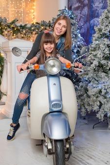 Kleines süßes mädchen mit mutter, die auf einem motorrad zusammen in weihnachten sitzt