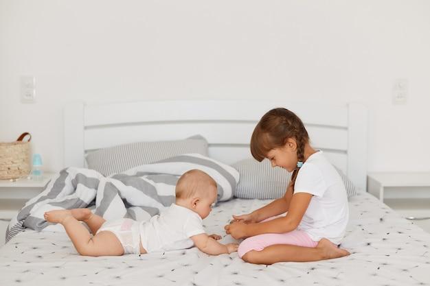 Kleines süßes mädchen mit weißem t-shirt und rosa shorts, das mit ihrer kleinen schwester spielt, während sie im hellen raum zusammen ist, glückliche kindheit, geschwister, die zeit miteinander verbringen.