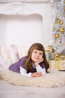 Kleines süßes mädchen nahe einem weihnachtsbaum
