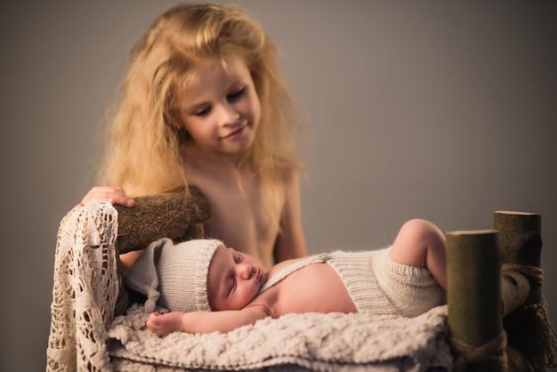 Kleines süßes mädchen schaut ihren neugeborenen bruder an, der auf einem plaid auf einem gemütlichen holzbett liegt