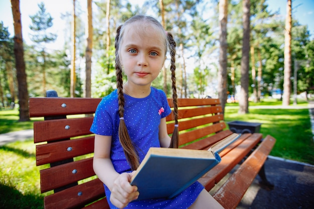 Kleines süßes mädchen sitzt auf einer bank und liest ein buch