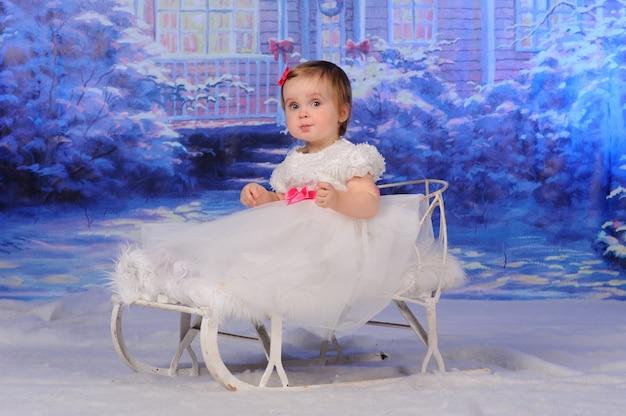 Kleines süßes mädchen sitzt in einem schlitten auf dem schnee.