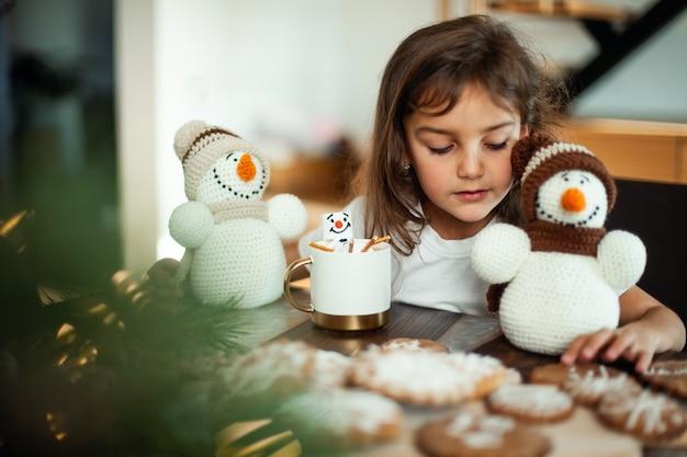 Kleines süßes mädchen spielt mit gestrickten schneemännern und isst lebkuchen und trinkt kakao mit marshmallows.
