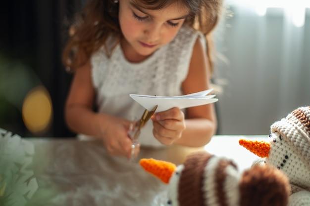 Kleines süßes mädchen und junge schöne frau schnitten schneeflocken aus weißem papier. lebkuchen und kakao mit marshmallows. das konzept der vorbereitung auf das neue jahr und weihnachten.