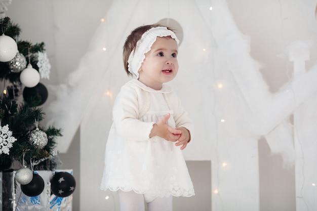 Kleines süßes mädchen verkleidet als engel nahe dem weihnachtsbaum mit geschenken für die neujahrsfeiertage