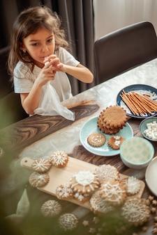 Kleines süßes mädchen verziert lebkuchen mit zuckerglasur. vorbereitung für das weihnachtskonzept.