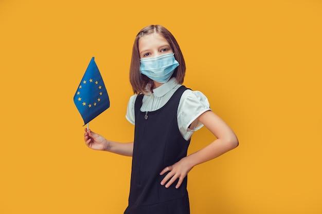 Kleines süßes schulmädchen in schutzmaske, das eine flagge des sicherheitskonzepts der europäischen union hält