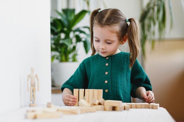 Kleines süßes vorschulmädchen spielt zu hause mit holzspielzeug auf dem tisch. natürliche taktilität entwicklung.