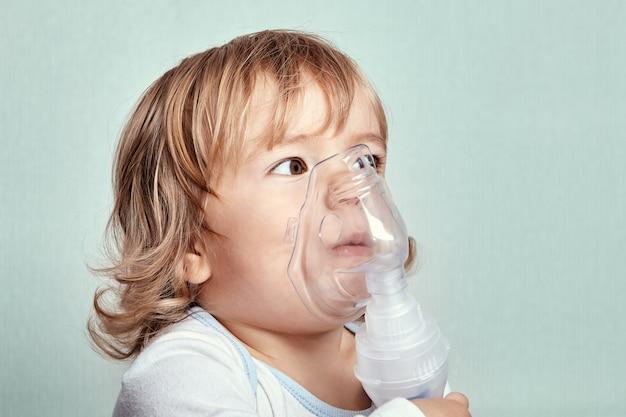 Kleines süßes weißes mädchen ungefähr 2 jahre alt verwendet vernebler, um einen asthmaanfall zu stoppen.