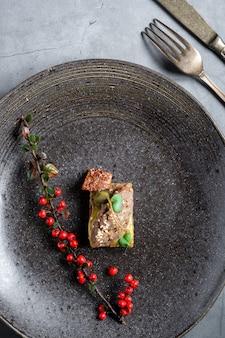 Kleines tapas-sandwich auf einem größeren dunklen teller auf einem konkreten tabellenhintergrund. verziert mit einem zweig mit roten beeren und einer gabel mit einem messer.