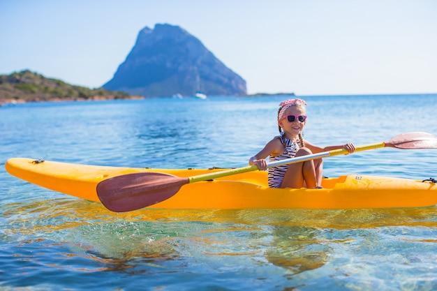 Kleines tapferes nettes mädchen, das im klaren blauen meer kayak fährt
