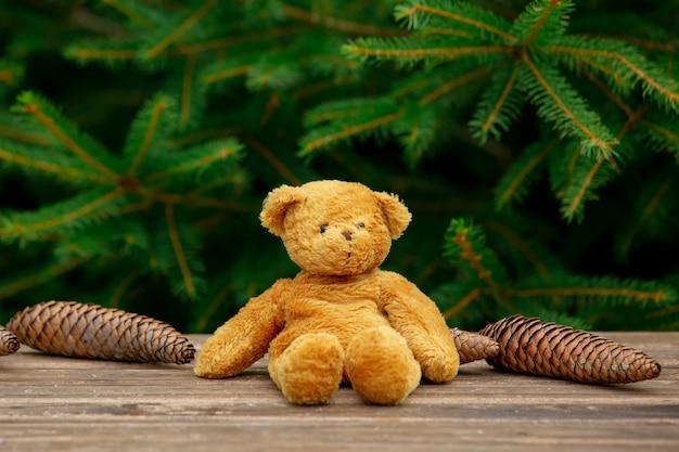 Kleines teddybärspielzeug auf holztisch mit fichtenzweigen auf hintergrund