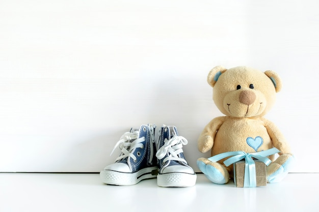 Kleines teddybärspielzeug mit geschenkbox auf weißem tischhintergrund mit kopienraum. babyparty, geschenk für jungen-kind-kind-geburtstag