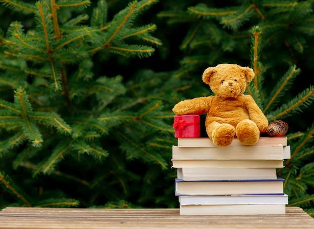 Kleines teddybärspielzeug und bücher auf holztisch mit fichtenzweigen auf hintergrund