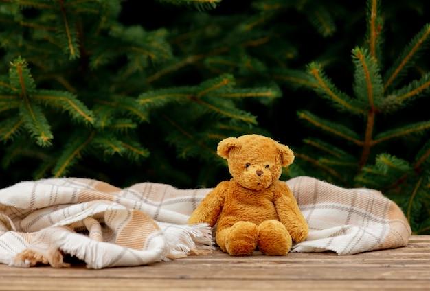 Kleines teddybärspielzeug und schal auf holztisch mit fichtenzweigen auf hintergrund
