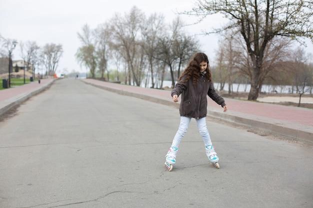 Kleines teenie-mädchen trägt frühlingsmantel und blue jeans-rollerblading auf der straße