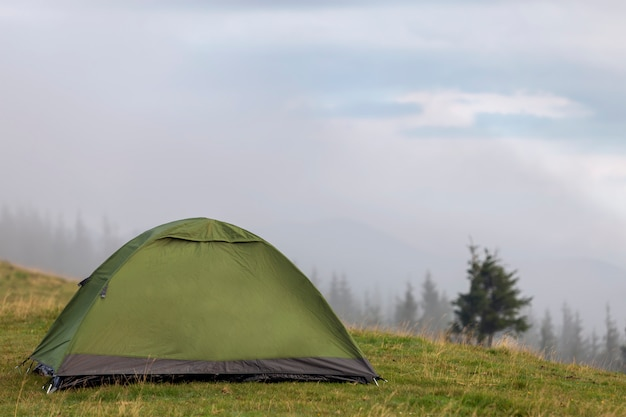 Kleines touristisches zelt auf grasartigem gebirgshügel. sommercamping in den bergen im morgengrauen. tourismus-konzept.
