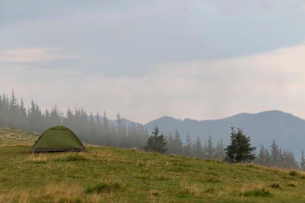 Kleines touristisches zelt auf grasartigem gebirgshügel. sommercamping in den bergen im morgengrauen.