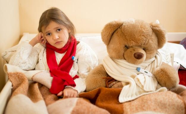 Kleines trauriges mädchen, das temperatur mit teddybär im bett misst
